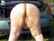 Fat woman pissing behind the car